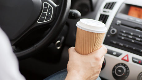 distracted driver in car with coffee cup in hand