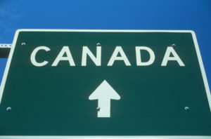 green traffic sign letters New Canadians Canada with arrow