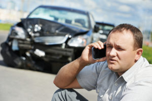 man on knees using cell phone after a vehicle accident