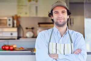 business owner in apron and wearing hat smiling in front of produce market business