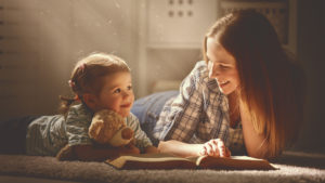 mother and baby son read book together on floor with light streaming into room