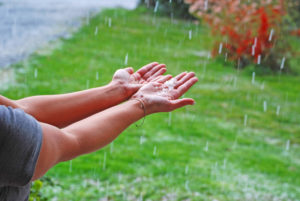 hands outside facing upwards as rain falls