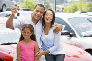 family of three husband wife and their daughter holding keys in front of red car