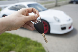 keys held in front of white porsche sports car