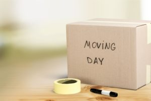 moving day written on box beside tape and permanent marker move