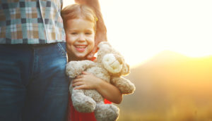 little smiling girl holding teddy bear next to parent in sunset