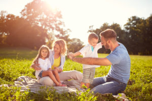 family of four having a picnic playing on green grass in sunshine