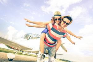 couple smiling in front of airplane