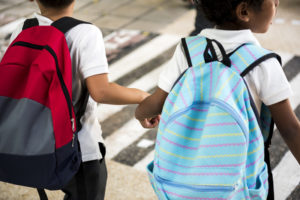 two kids with red and blue backpacks back to school